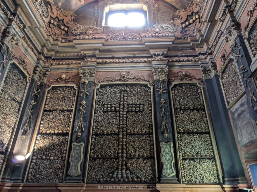 Picture of a wall covered with bones and skulls in the Ossuary Chapel of a church in Milan, Italy
